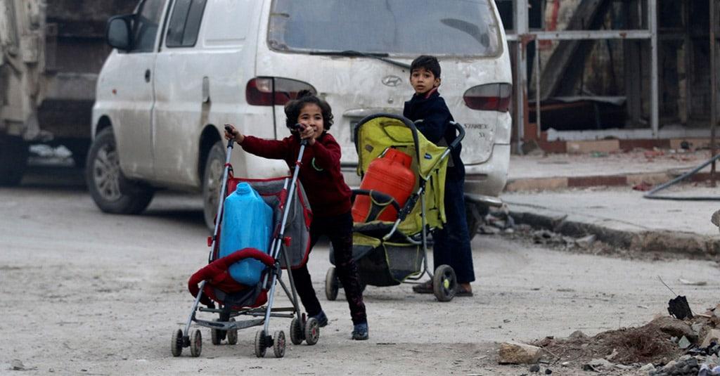 เด็กๆเข็นรถเข็นบรรทุกถังน้ำในขณะหลบหนีลึกเข้าไปในพื้นที่กลุ่มกบฏส่วนที่เหลือในอาเล็ปโป
